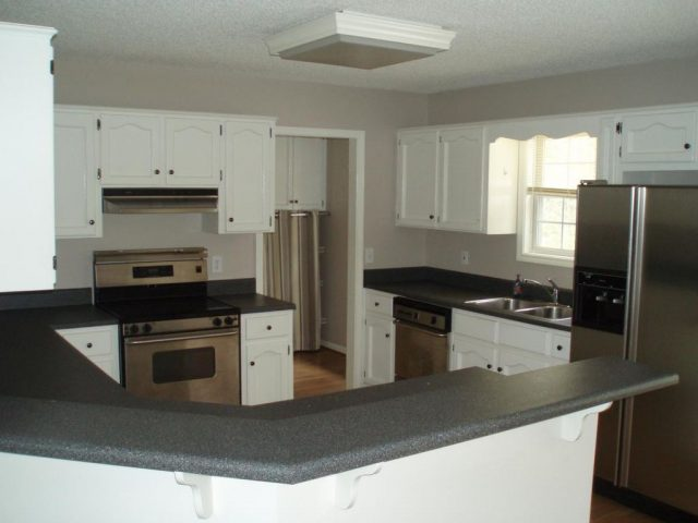 white kitchen bar and stainless appliances